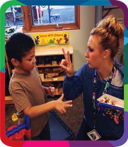 Teacher holding up two fingers to a child in a classroom.