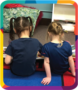 The backs of two little girls reading a book together.